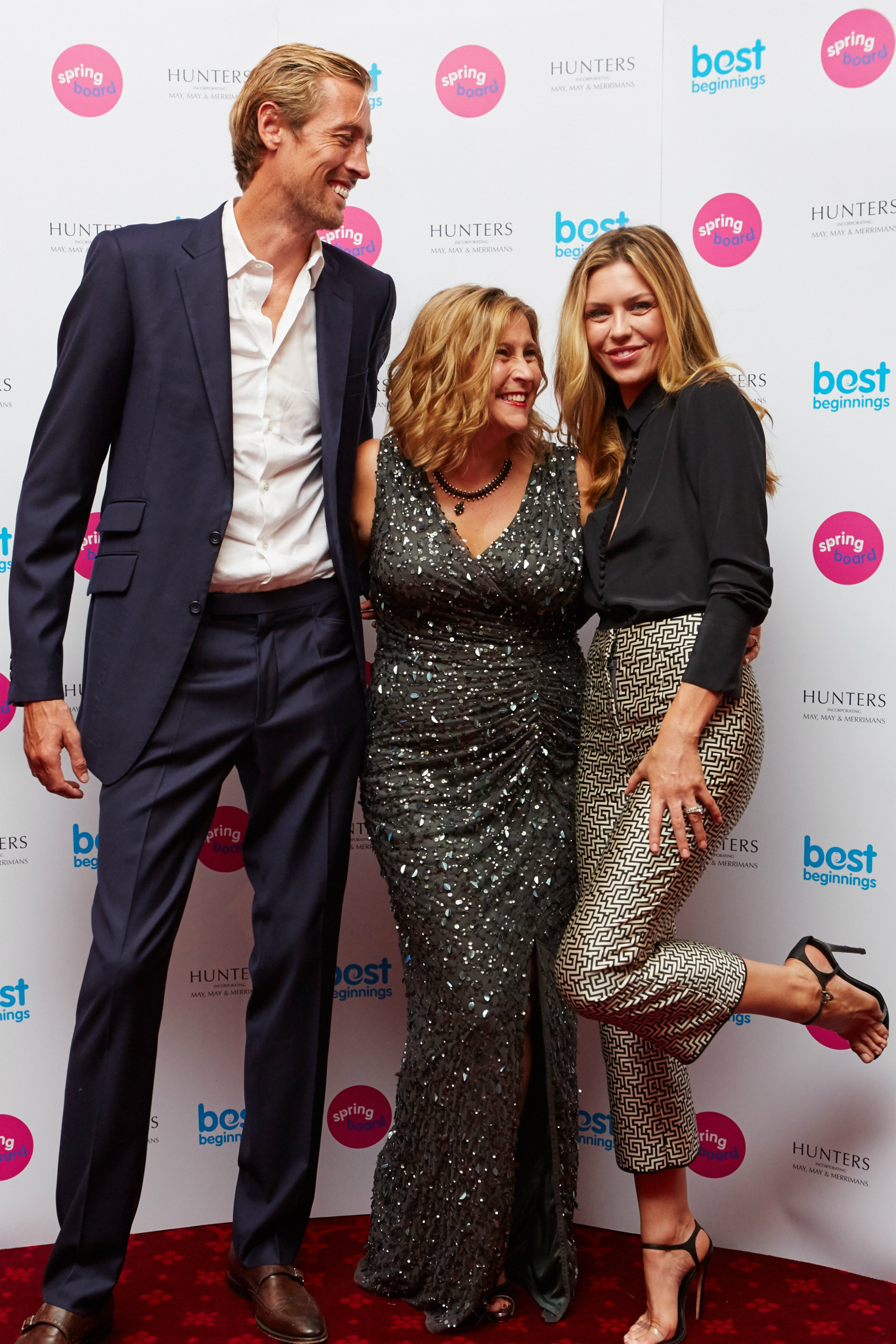 Footballer Peter Crouch (L) and his wife, model and TV presenter Abbey Clancey (R) share a joke with Best Beginnings CEO, Alison Baum, at the Springboard launch event.